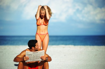 Young couple arguing on beach, man holding newspaper